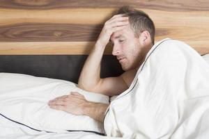 tiro brilhante de homem chateado encontra-se na cama foto