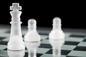 rei do xadrez e peão no tabuleiro de xadrez foto