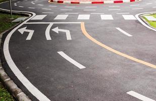 símbolo de seta em uma superfície de estrada de asfalto preto foto