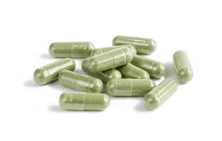 cápsulas de produto de suplemento de ervas verde isolado no branco