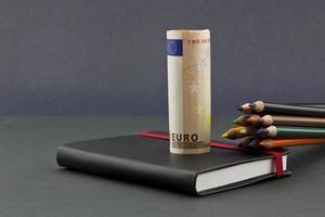 vários lápis de cor com moeda euro e jornal preto foto