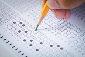 mão preencher lápis e folha de computador de papel de exame foto