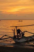 barco de pescador asiático primitivo ao pôr do sol foto