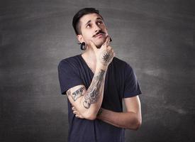 belo homem tatuado pensando foto
