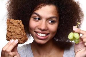 senhora afro escolhendo entre dois tipos de comida foto