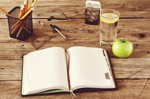 caderno em branco aberto sobre fundo de madeira foto
