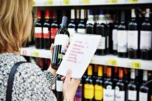 garota escolhe garrafa de vinho para data na loja foto
