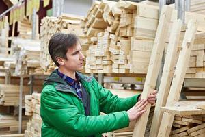 homem comprando madeira na loja de bricolage foto