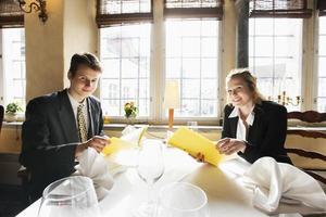 retrato de casal de negócios sorridente com menus na mesa do restaurante foto