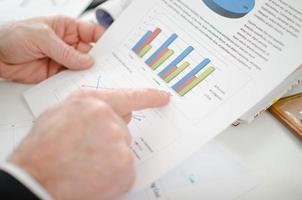 empresário, apontando um gráfico com o dedo indicador foto