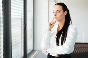 executivo de mulher em pé junto à janela e olhando através dela foto