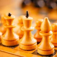 xadrez de madeira antiga em pé no tabuleiro de xadrez foto