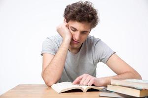 estudante do sexo masculino cansado sentado à mesa foto