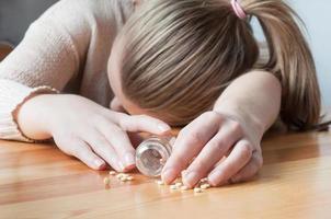 pílulas derramadas fora de mão foto