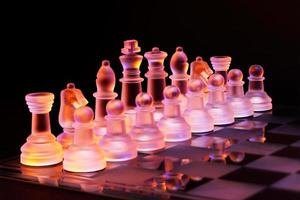 xadrez de vidro no tabuleiro de xadrez iluminado pela luz azul e laranja foto