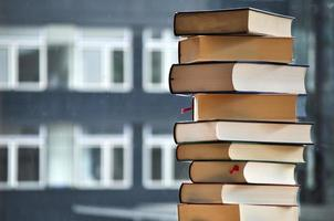 pilha de livros com edifício turva no fundo