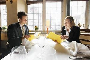 casal jovem negócios com menus na mesa do restaurante foto