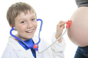 alegre irmãozinho ouvindo estetoscópio barriga
