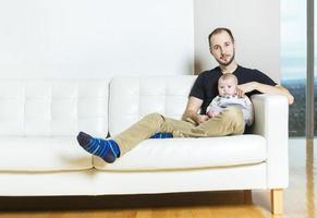 pai com bebê no sofá, tendo um bom tempo