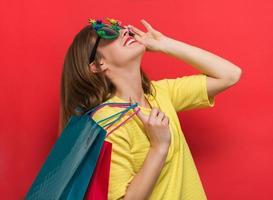 mulher com óculos de festa de Natal e sacolas de compras foto