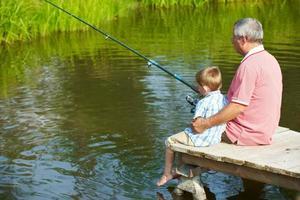 velho e menino pescando no lago foto