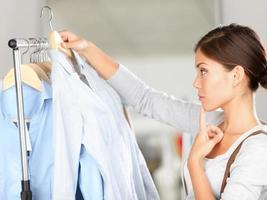 comprador escolhendo roupas pensando foto