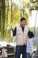pai e filho exibindo capturas de pesca no lago foto
