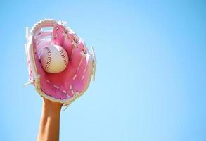 mão de jogador de beisebol com luva rosa e bola foto