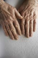 mãos de mulher idosa, lendo um livro com linguagem braille foto