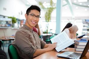homem sentado à mesa com o livro na Universidade foto