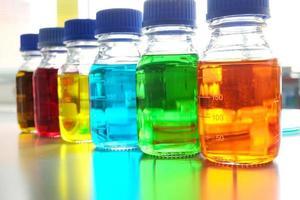 líquido colorido em frasco para uso de laboratório em cima da mesa foto