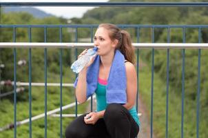 jovem mulher bebendo água engarrafada foto