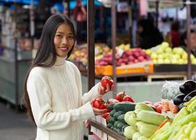 jovem mulher segurando tomates no mercado de vegetais foto
