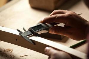 carpinteiro medindo parte da cadeira com pinças elétricas. foto