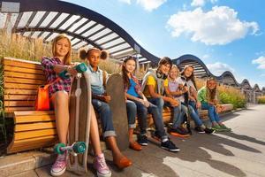 vista de crianças felizes, que se sentam no banco de madeira foto