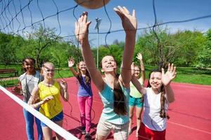 equipe de adolescentes jogando vôlei na quadra foto