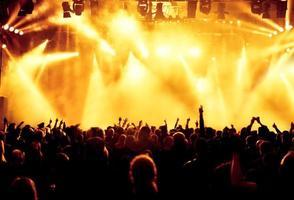uma multidão em um concerto com luzes amarelas e nevoeiro