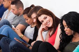 bela estudante sentado com colegas foto