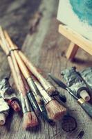 pincéis artísticos, tubos de tinta, paleta e cavalete.