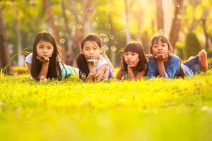 filhos bonitos se divertindo bolha no gramado verde foto