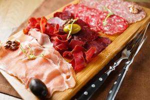 variedade de carnes, salsichas, salame, presunto, azeitonas foto