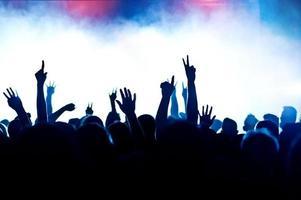 multidão de concertos em silhueta por luzes do palco e fumaça