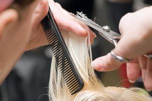 estilista cortando o cabelo loiro de uma criança com uma tesoura foto