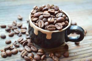 copo cheio de grãos de café na mesa de madeira foto