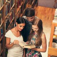 grupo de estudantes na biblioteca lendo livros foto