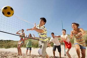 amigos adolescentes jogando vôlei na praia foto