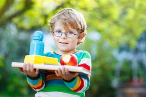menino de escola com livros, maçã e garrafa de bebida foto