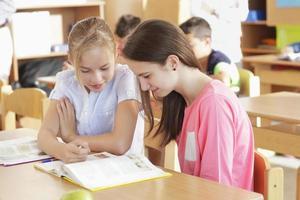 as crianças estão sentadas na sala de aula foto