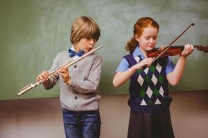 alunos tocando flauta e violino na sala de aula
