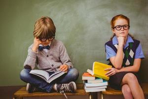 crianças com pilha de livros em sala de aula foto